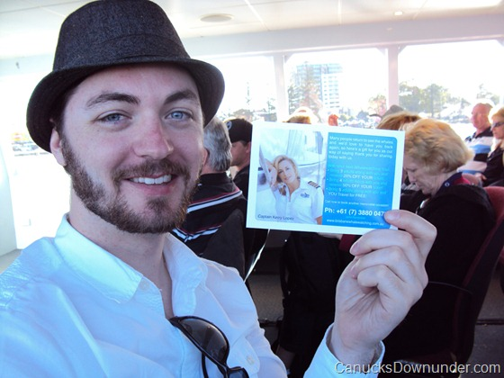 Jason holding up the Brisbane Whale Watching postcard with a glamour shot of Captain Kerry